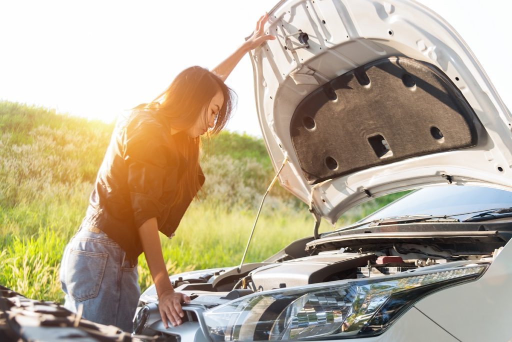 Woman checking her overheating car engine