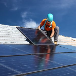 man installing solar panels on the roof