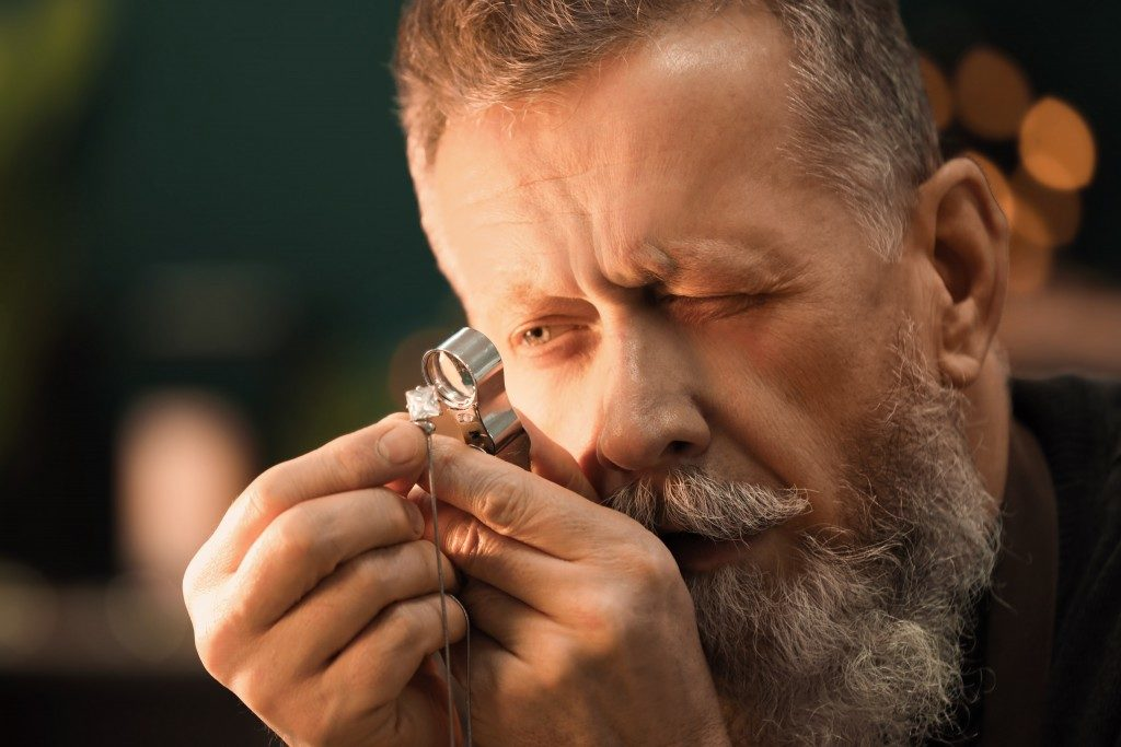 Jewelry maker inspecting jewelry