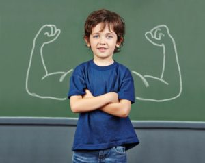 Strong child with muscles drawn on chalkboard