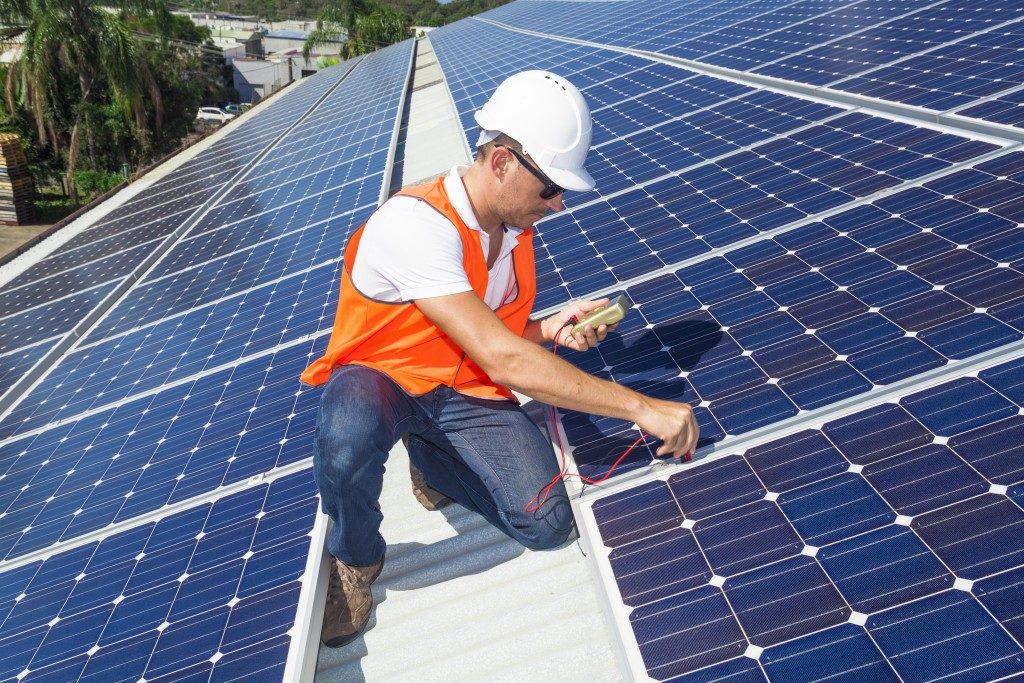 technician checking solar panels on roof